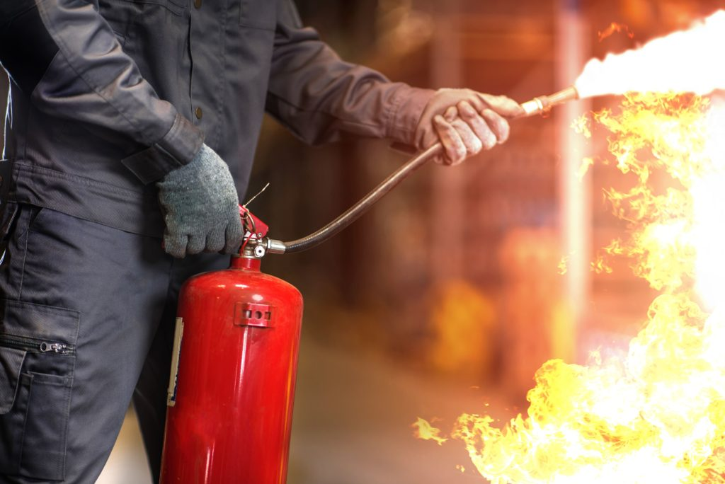 Man using a fire extinguisher to control a fire